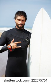 Portrait of hipster guy with white surfboard standing on ocean the beach, professional surfer man dressed in wetsuit ready to surfing on big waves, happy surfer holding his board at sunny summer day