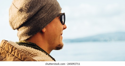 Portrait of hipster handsome young man on background of sea
