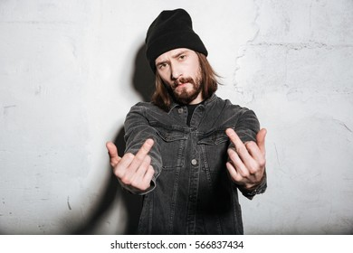 Portrait of a hipster man in hat showing fuck you sign isolated over wall background