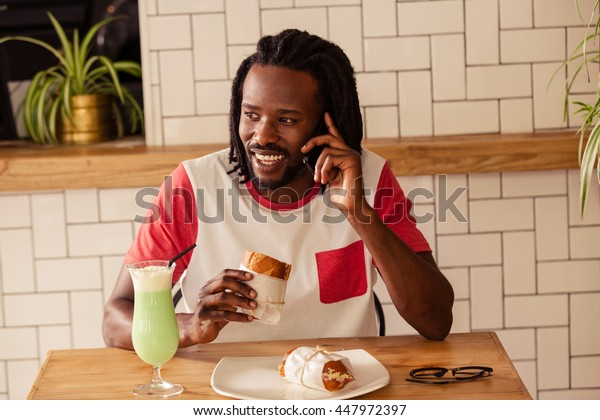 Portrait of hipster man on the phone while eating at cafe