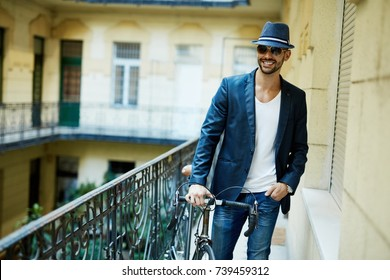 Portrait of hipster man in sunglasses and hat with bicycle leaving home in urban apartment building.