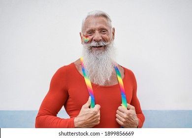 Portrait of hipster senior man laughing at gay pride parade - Concept of lgbt and homosexual love
