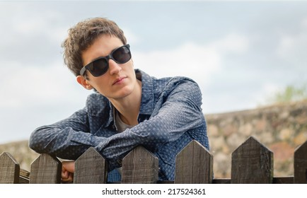 Portrait of hipster teenager with sunglasses posing outdoors over a wooden fence