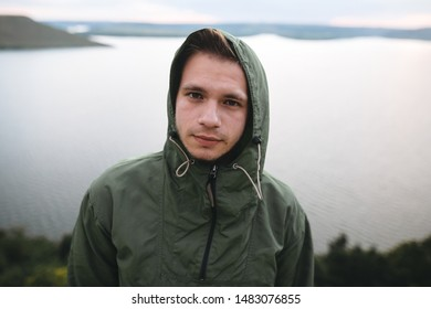 Portrait of hipster traveler in green windbreaker on top of rock mountain with amazing view on river. Stylish guy exploring and traveling. Atmospheric moment. Copy space