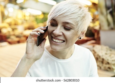 Portrait of  hipster woman with blonde short hair happy talking by mobile phone. Indoor botanical garden interior or summer park