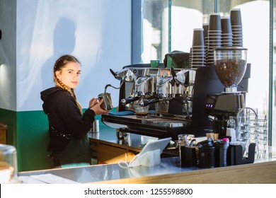 Portrait of hipster young woman working professional barista while preparing coffee beverage for client on modern machine. Positive female waiter with two braids in green apron working intently.
