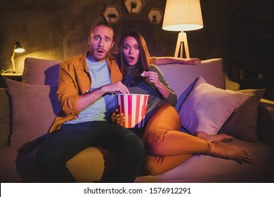 Portrait of his he her she nice attractive lovely scared afraid frightened married spouses sitting on divan watching horror genre film resting at home house apartment living-room indoors