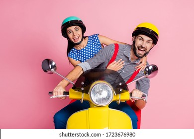 Portrait of his he her she nice attractive childish comic cheerful cheery couple driving moped having fun fooling isolated over pink pastel color background