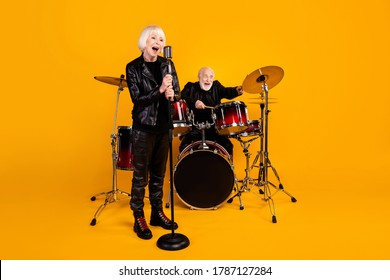 Portrait of his he her she nice attractive cheerful excited glad grey-haired couple giving live concert having fun performing isolated over bright vivid shine vibrant yellow color background