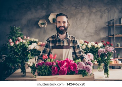 Portrait of his he nice attractive cheery cheerful content guy professional company founder enjoying holding big large box peony tulip diverse at industrial loft concrete style indoors