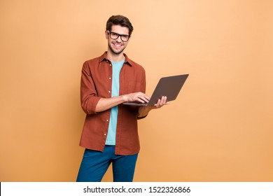 Portrait of his he nice attractive cheerful cheery successful content smart clever brunet guy agent broker holding in hands laptop working isolated over beige color pastel background - Shutterstock ID 1522326866