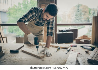 Portrait of his he nice attractive serious focused hardworking experienced guy repairman drilling creating new house building project order gift shop at modern industrial loft style interior
