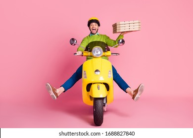 Portrait of his he nice attractive lovely funky creative cheerful cheery guy driving moped fooling having fun delivering pizza pie isolated over pink pastel color background