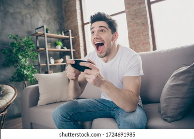 Portrait of his he nice attractive glad crazy addicted cheerful cheery muscular guy playing game having fun free time at modern industrial loft brick interior style living-room