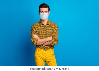 Portrait of his he nice attractive content serious conscious guy wearing gauze mask checked shirt disease preventive measures folded arms isolated bright vivid shine vibrant blue color background