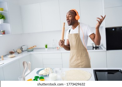 Portrait of his he nice attractive cheerful dreamy funky guy meloman making handmade pie cake using pin mic singing hit melody in modern light white interior house kitchen