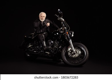 Portrait of his he nice attractive content serious grey-haired dude hipster traveler sitting on chopper spending weekend exploring world tour trip insurance isolated black color background