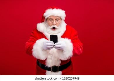 Portrait seines hübschen, gut aussehenden und erstaunlichen Weihnachtsmanns mit Gadget 5g Blog Blogger mit schneller Geschwindigkeit Surfen in Multimedia einzeln auf hellblühendem, lebendigem, rotem Hintergrund
