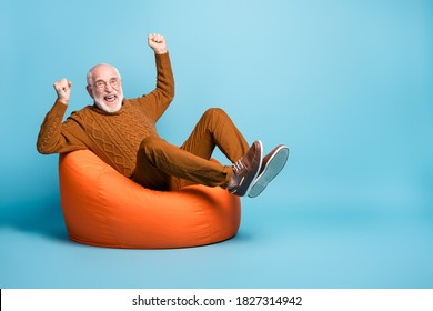 Portrait of his he nice attractive cheerful cheery glad excited lucky bearded grey-haired man sitting in bag chair rejoicing having fun isolated over blue pastel color background