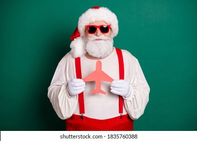 Portrait of his he nice handsome funky fat overweight Santa going on weekend, holding in hand paper plane form shape tour resort tourism voyage isolated over green color background