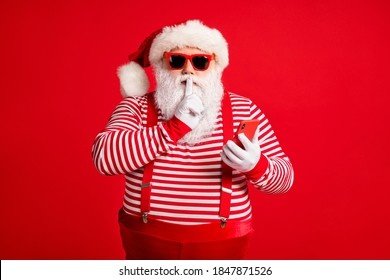 Portrait of his he nice handsome mysterious bearded fat Santa using device app 5g shopping secret sale discount showing shh sign silence mute isolated bright vivid shine vibrant red color background