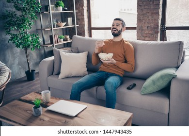 Portrait of his he nice-looking attractive bearded cheerful cheery positive guy spending weekend sitting on divan watching tv at industrial loft interior style living-room indoors