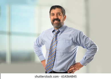 Portrait of Hispanic businessman with hands on hips inside office