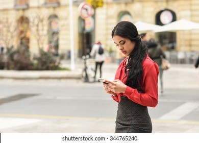 Portrait of hispanic businesswoman in urban background looking at her mobile phone