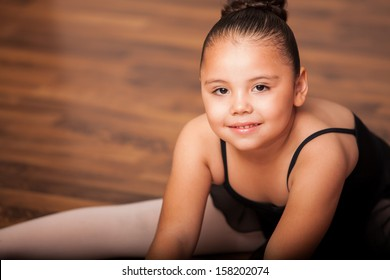 Portrait of a Hispanic and chubby little girl wearing a ballet outfit and smiling