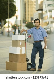 Portrait of an Hispanic delivery man on city sidewalk with hand truck full of boxes to deliver
