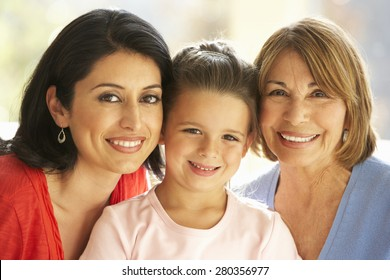 Portrait Of Hispanic Grandmother, Mother And Daughter Relaxing At Home