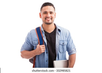 Portrait of Hispanic guy going to a university carrying a backpack and a laptop computer on a white background