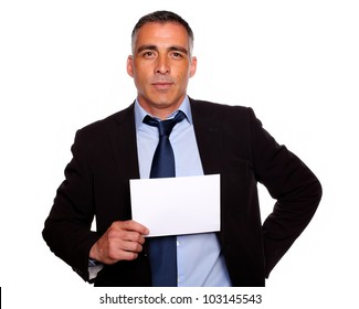 Portrait of a hispanic senior business man with a black suit holding a white card with copyspace against white background