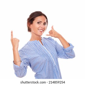 Portrait of hispanic woman with call gesture pointing up while smiling at you on isolated white background - copyspace
