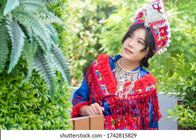 portrait of Hmong young woman looking up in tradition Hmong costume for young girl; Asian ethnic tribal people in traditional clothing culture of Hmong or Miao people in east and southeast Asia