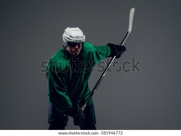 Portrait of hockey player holds ice stick isolated on grey background.