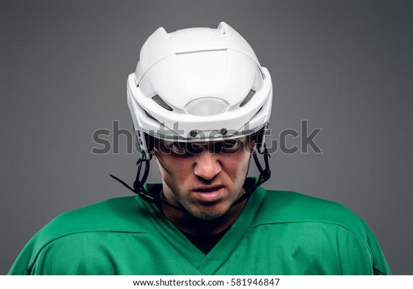 Portrait of hockey player isolated on grey background.