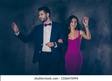 Portrait of hollywood lady in tight violet dress, handsome vip man in tuxedo with bow attractive superstars holding hands go along the red carpet wagging with palm isolated grey background spotlight