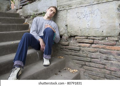 Portrait of an homeless man against a wall.
