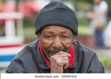 Portrait of homeless man thinking while sitting outdoors during the daytime