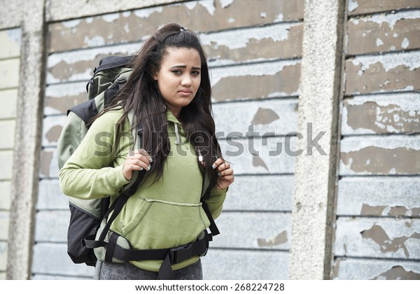 Portrait Of Homeless Teenage Girl On Street With Rucksack