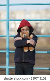portrait of a homeless young boy with bear