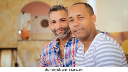 Portrait of homosexual couple, happy gay people smiling at camera, sitting on sofa at home. Same sex marriage between hispanic men.