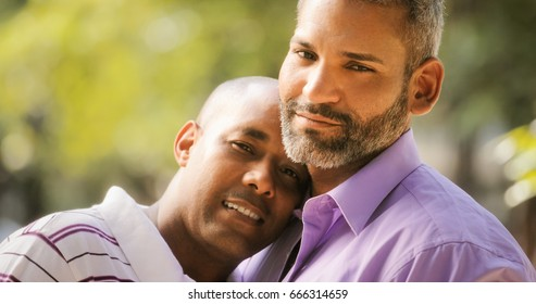 Portrait of homosexual couple hugging outdoor and looking at camera. Same sex marriage between hispanic men.