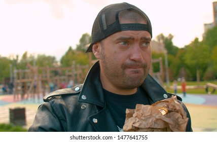 Portrait of a hooligan in the biker jacket illegally drinking beer on the kid's playground