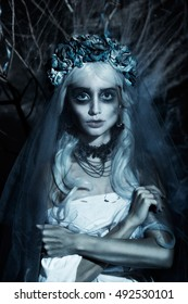 Portrait of a horrible scary Corpse Bride in wreath with dead blue flowers and halloween makeup. Dark horror background of gloomy forest and branches festooned with cobwebs.