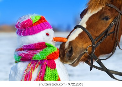 Portrait of horse and snowman in winter landscape.