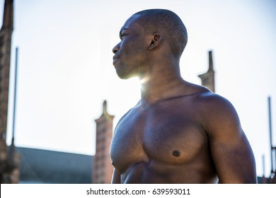 Portrait of a hot black man shirtless in urban environment, walking on metal stairs, looking away to a side