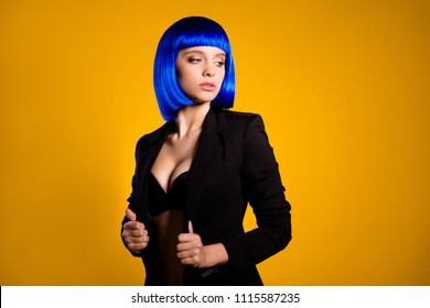 Portrait of hot confident lady in black jacket vivid blue wig demonstrate her big sexy decollete boobs looking away isolated on yellow background with shadow