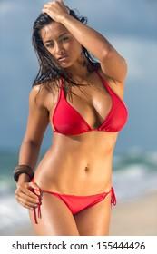 Portrait of hot female in red bikini posing over the blurred beach background